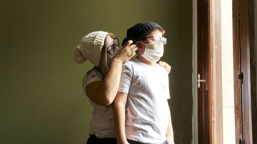 Mother with a child in medical masks looking out the window.