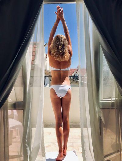 Rear view of woman wearing bikini while standing in balcony