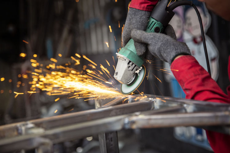 Welder used grinding stone on steel in factory with sparks, welding process at the industrial work