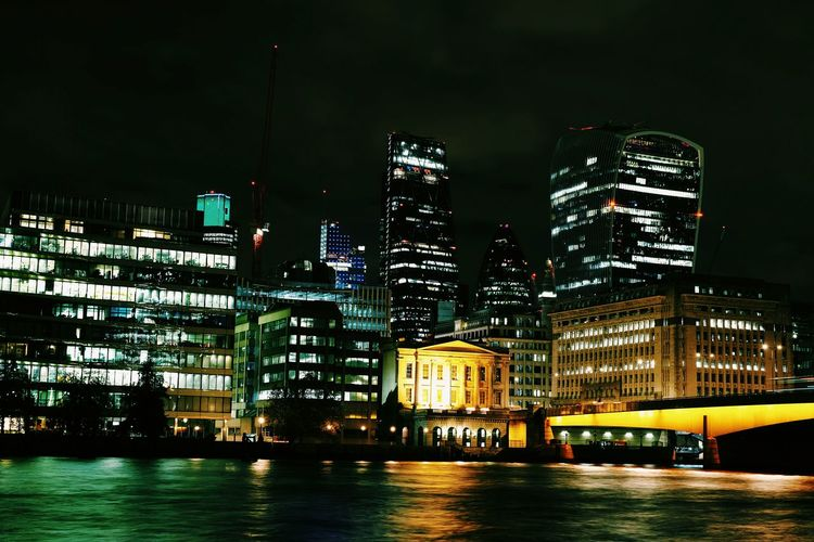 Illuminated 30 st mary axe and thames river in city at night