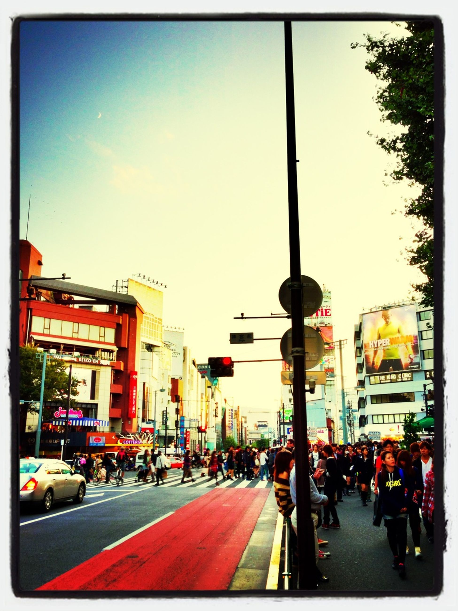 street, transfer print, transportation, city, building exterior, car, architecture, land vehicle, city life, built structure, city street, road, mode of transport, auto post production filter, incidental people, sky, large group of people, traffic, person