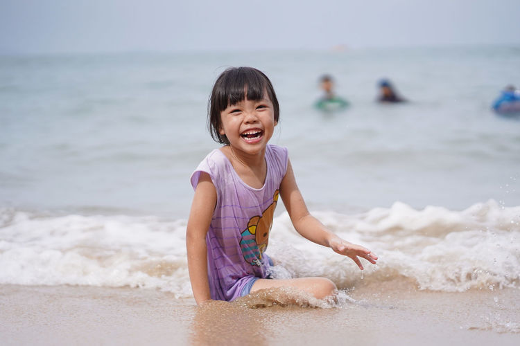 Beach Child Childhood Cute Emotion Focus On Foreground Fun Girls Happiness Horizon Over Water Innocence Land Leisure Activity Lifestyles Outdoors People Real People Sand Sea Smiling Water