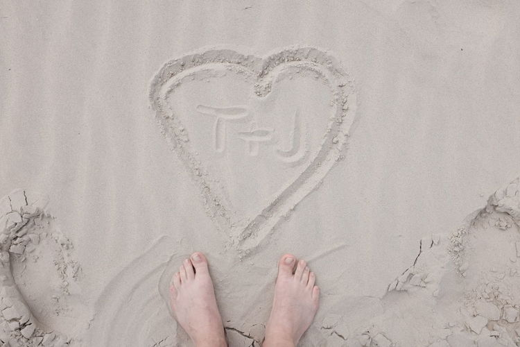 Low section of person standing by heart shape on sandy beach