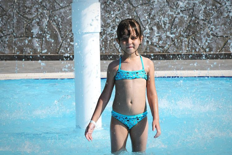 Portrait of girl standing in swimming pool