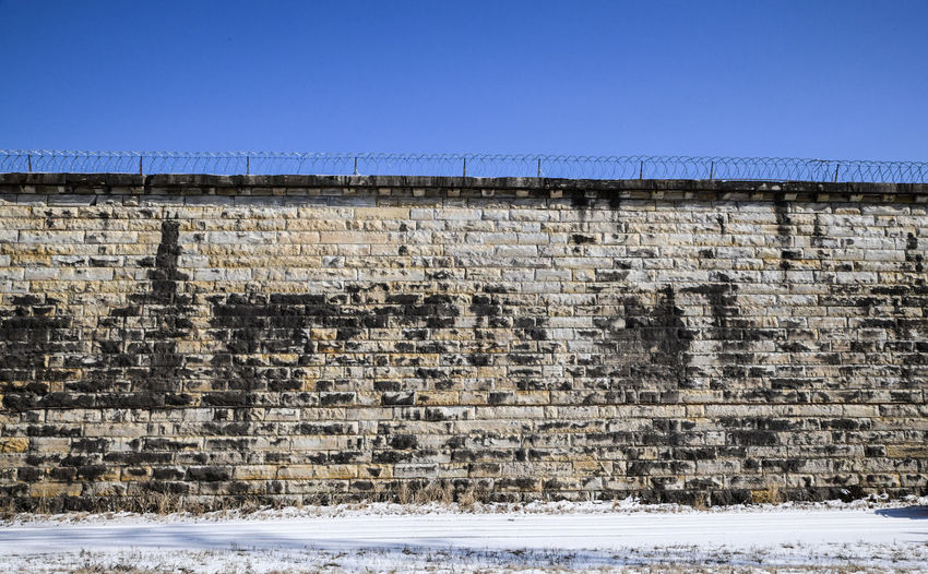Abandoned prison wall brick and blue sky