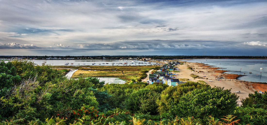 Houses on shore at mudeford against cloudy sky