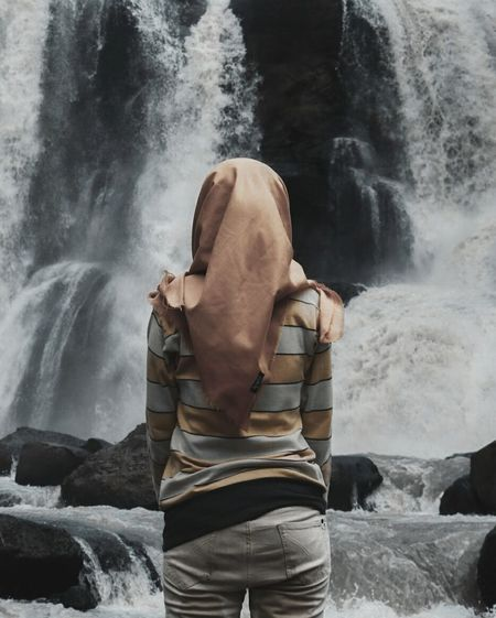 Rear View Of Woman Against Waterfall