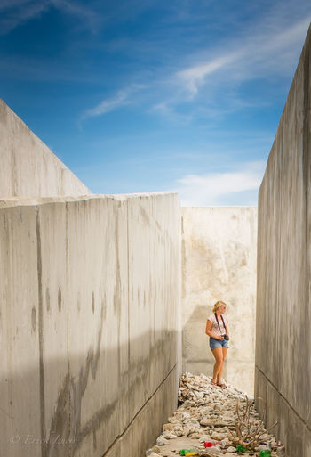 Young woman standing amidst concrete wall