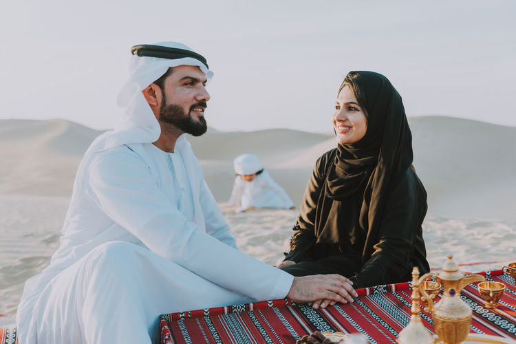 Smiling couple with tea sitting on carpet against son playing at desert