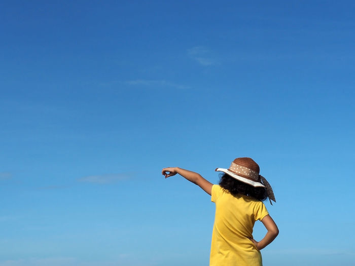Rear view of girl pointing standing against blue sky