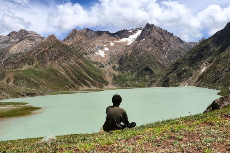 Rear view of man sitting on mountain by lake against sky
