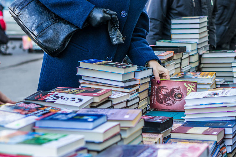 Cropped image of woman standing by bookstall