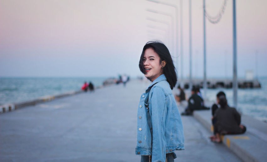 Side view portrait of cheerful young woman standing on promenade against sky during sunset