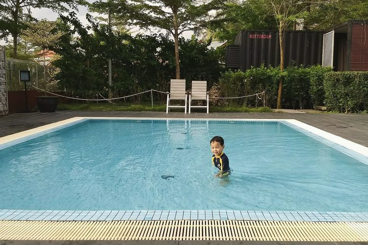 A young kid playing alone in a swimming pool Poolside Chairs Vacation Travel Destinations Water Playing Refreshing Swimming Pool Childhood Children Only Child Outdoors One Person Leisure Activity Day Enjoyment People One Boy Only Swimming