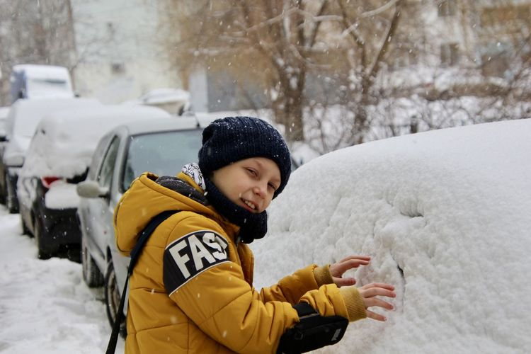 Portrait of boy by snow on car during winter
