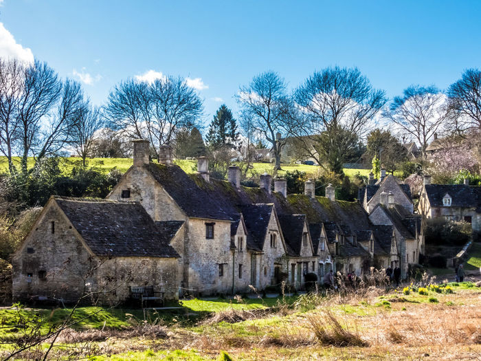 Arlington Row is one of the most photographed village streets in the UK -- Bibury, Gloucestershire Tree Plant Architecture Sky Built Structure Nature No People History Building Exterior Day Sunlight The Past Field Land Building Grass Cemetery Tombstone House Bare Tree Outdoors Bibury Arlington Row, Cotswolds Uk