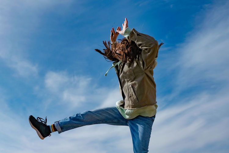 Low angle view of person jumping against sky