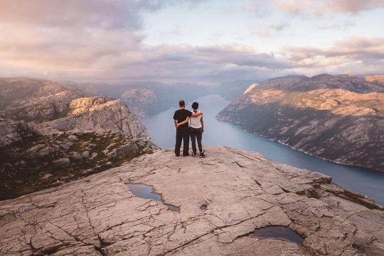 Full length of friends on rock against sky
