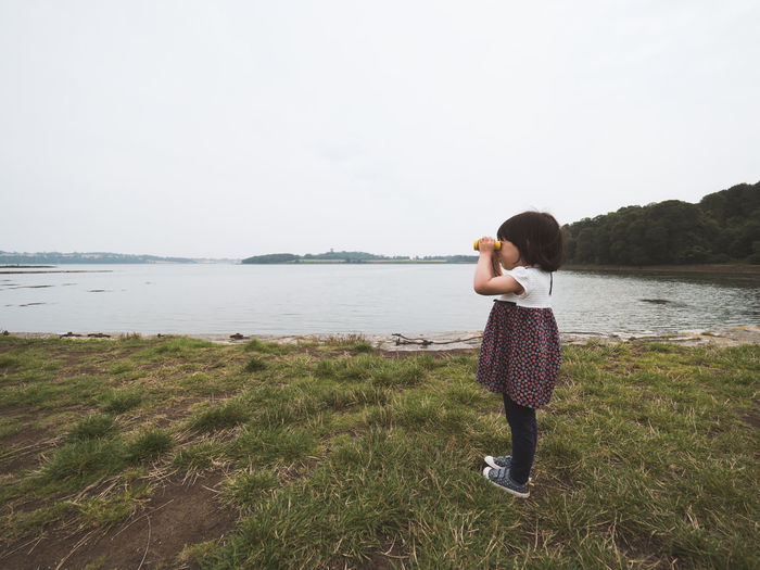 Full length of young girl standing on shore and looking against sky