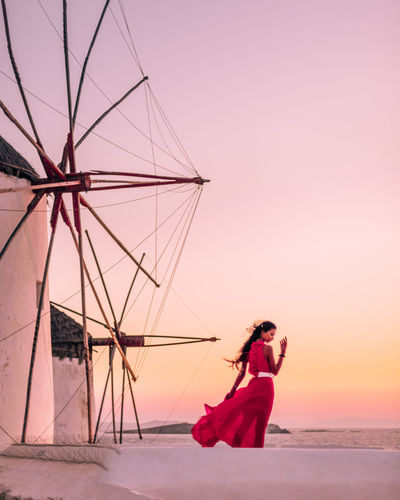 Rear view of woman standing by windmill against sky during sunset