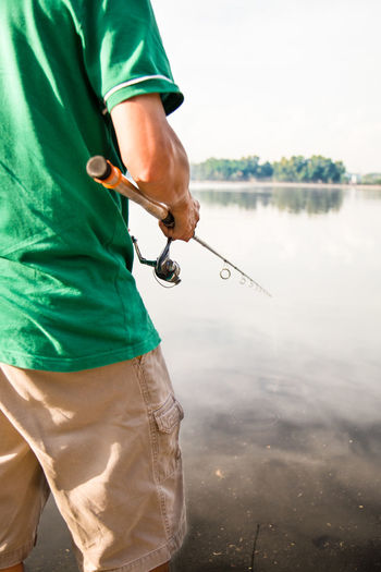 Midsection of man fishing in lake