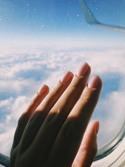 Close-Up Of Woman Hand On Airplane Window