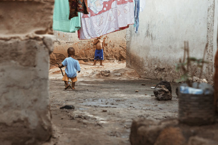 Two children playing in the streets Children Playing Slum Bearfoot Dirty Street Hanging Clothes Kids Kids Being Kids Exploring Fun Walking Real People Full Length Day Built Structure Child Childhood Selective Focus Wall - Building Feature Focus On Background Building Exterior Casual Clothing Outdoors Boys Fun Enjoying Life Springtime Decadence