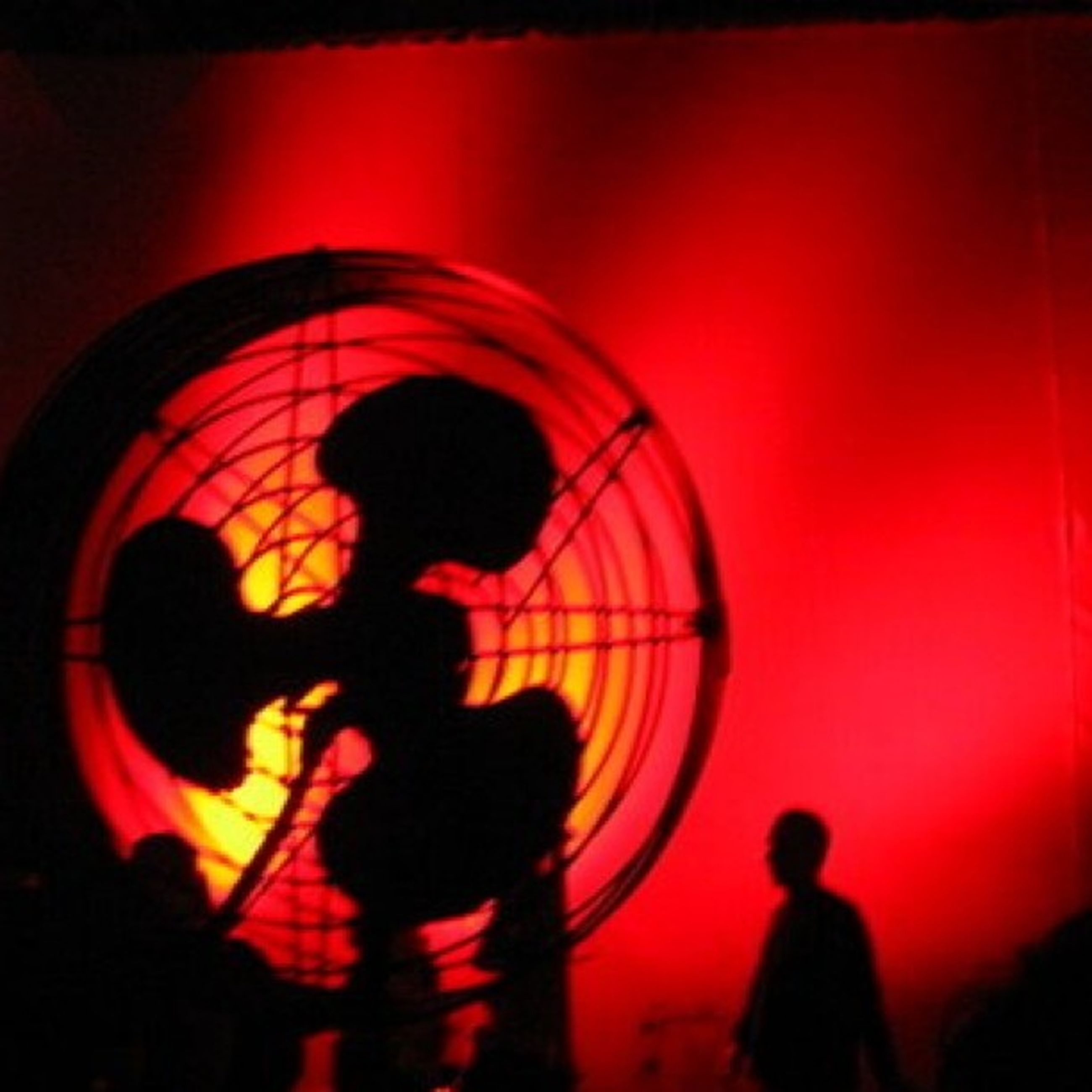 leisure activity, lifestyles, men, illuminated, arts culture and entertainment, person, silhouette, red, indoors, night, standing, enjoyment, circle, fun, rear view, walking, large group of people, orange color