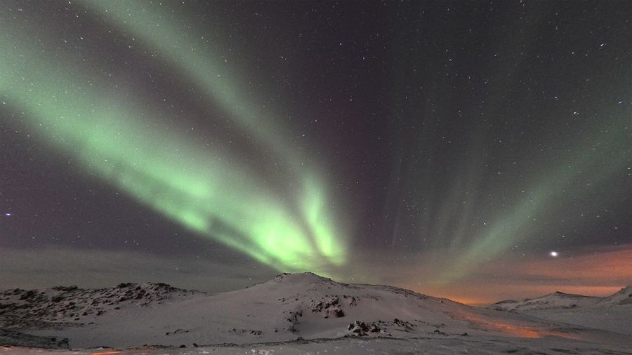 Scenic View Of Aurora Borealis Over Mountains During Winter