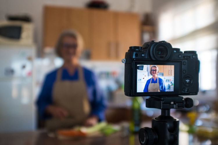 Close-up of camera filming woman at home