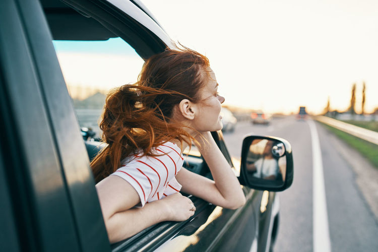 Side view of girl with car on window