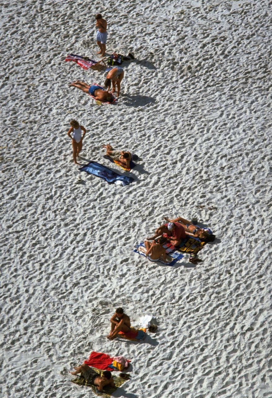 High Angle View Of People Relaxing At Sandy Beach