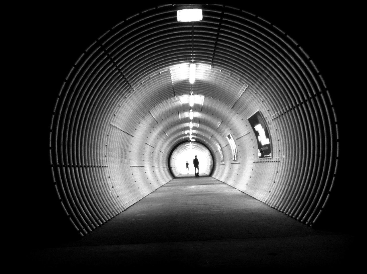 Silhouette people in illuminated tunnel