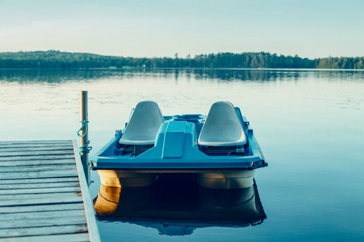 Old blue pedal boat tied to wooden dock pier at canadian ontario lake in muskoka. travel canadian