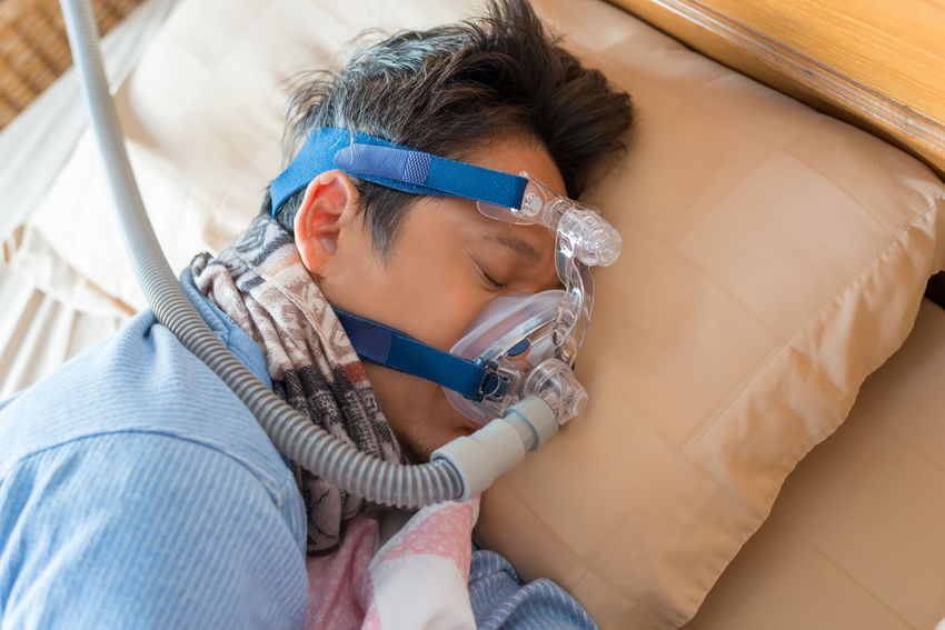 Man and cpap mask.Middle aged man with obstructive sleep apnea symptoms sleeping well on his left side by wearing cpap mask,healthcare concept. Choking Continuous Positive Airway Pressure Snoring Tube Concept Cpap Healthy Lifestyle High Angle View Left Side Mask Obstructive Sleep Apnea Real People Senior Men Sleep Apnea Sleeping Symptoms