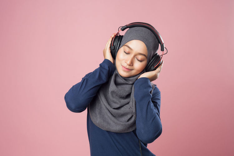 Young Woman Listening Music Against Pink Background