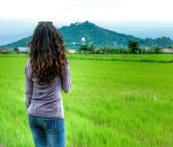 Rear view of woman standing on landscape