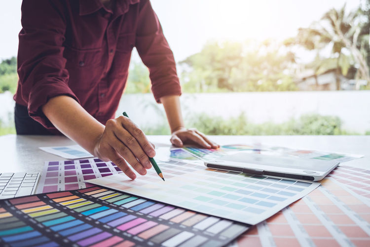 Architecture Adult Color Chart Colorful Creativity Day Designer  Drawing Focus On Foreground Graphic Design Hand Holding Human Body Part Human Hand Indoors  Lifestyles Men One Person Pantone Paper Pointing Swatch Technology Women