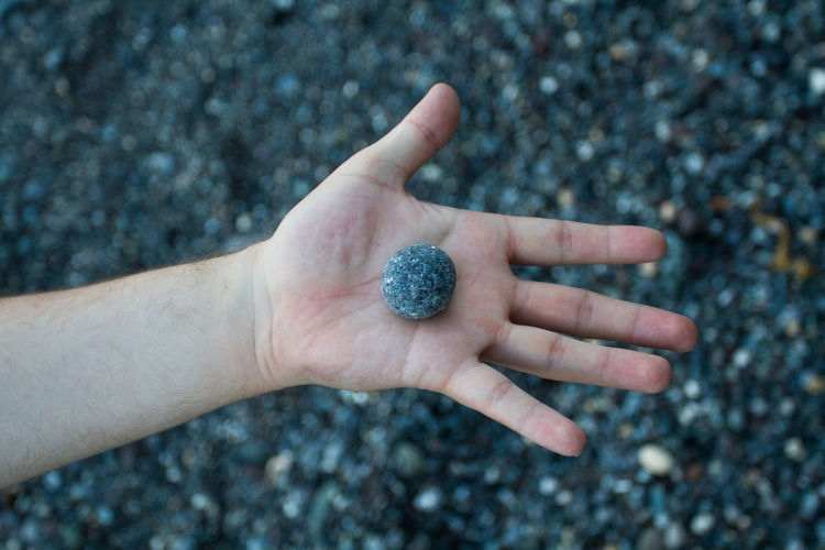 Cropped hand holding pebble at beach