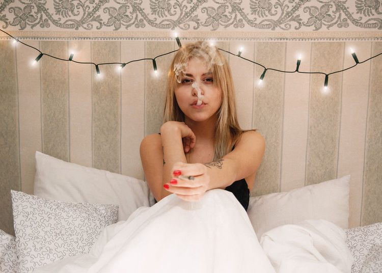 Portrait of young woman exhaling smoke while sitting on bed