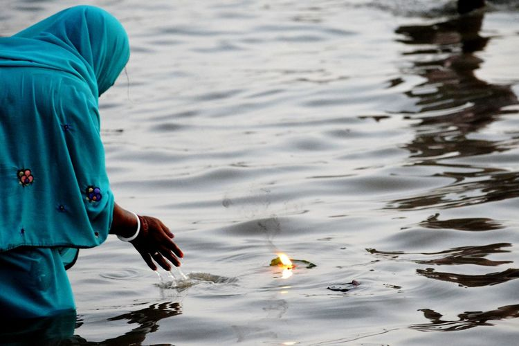 Woman standing by floating candle in river