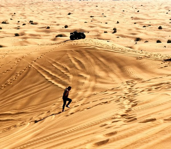 High Angle View Of Man Walking On Sand Dune