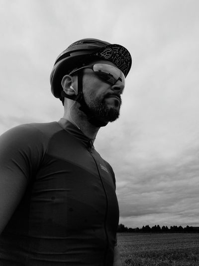 Low angle view of man wearing cycling helmet on field against cloudy sky