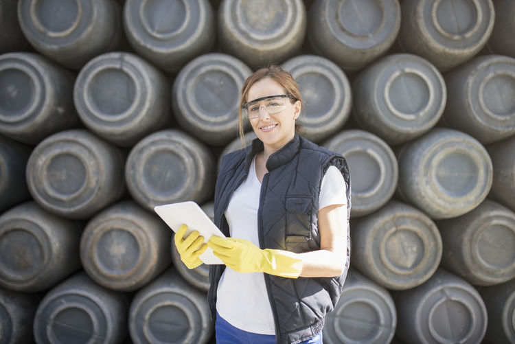 Portrait of smiling woman holding digital tablet while standing containers