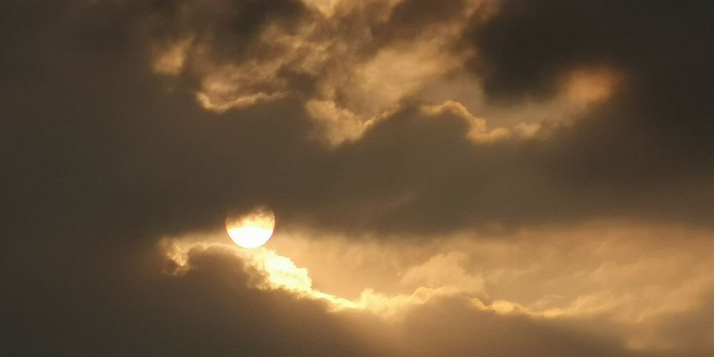 Low angle view of sun in sky during sunset
