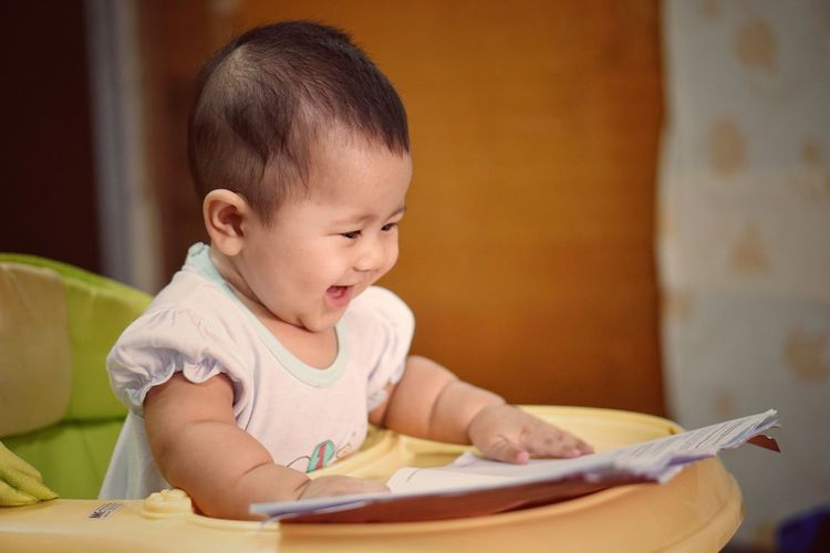 Close-up of cheerful baby girl with book on high chair