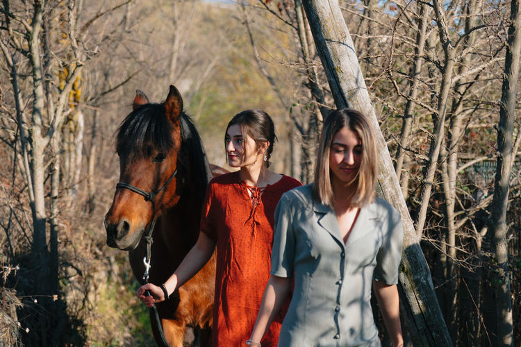 Young women with horse walking amidst trees