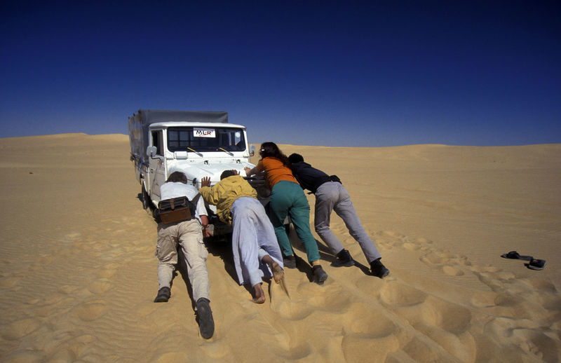 Men and women pushing jeep at desert against clear blue sky