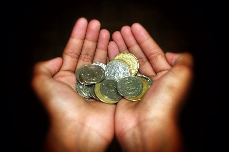 Close-Up Of Hands Holding Coins