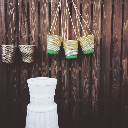Wicker baskets hanging against picket fence